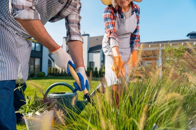 協力。庭にいる間一緒に働く快適な引退した妻と夫