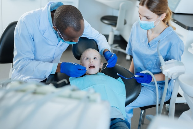 調整された仕事。看護師が唾液排出装置を持っている間、彼女の小さな患者の口腔の検査を行う快適な男性歯科医