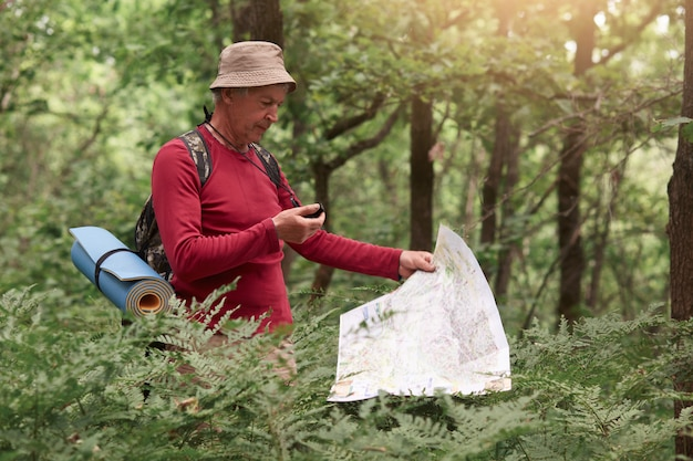 Coordination and navigation in the forest. image of man holding compass and paper map in his hands, finding right way in wood