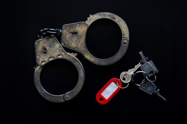 Наручники полицейского с ключами и биркой на черном