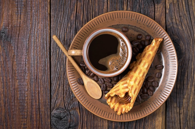 Cop of hot coffee and waffle cones with condensed milk in plate on old wooden table, top view