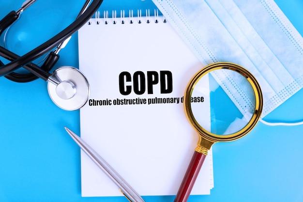 Copd 만성 폐쇄성 폐 질환, 청진기와 의료용 마스크가있는 노트북에 쓰여진 텍스트. 의료 개념.