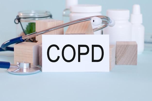 청진 기, 녹색 꽃, 의료 약 및 파란색 배경에 나무 블록 흰색 의료 카드에 쓰여진 경찰 단어