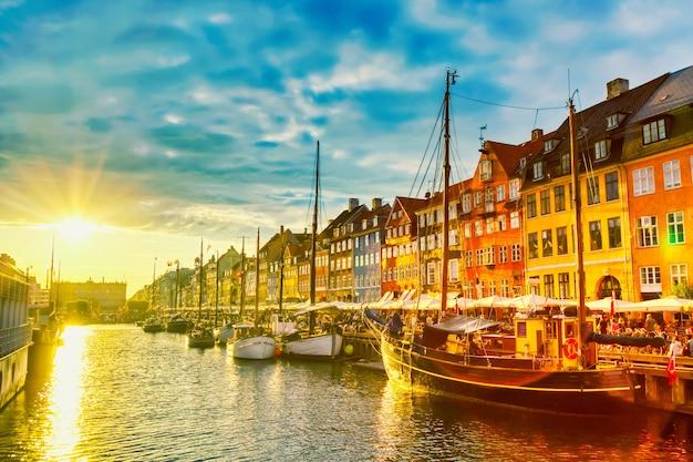コペンハーゲンの象徴的なビュー。日没時にデンマークのコペンハーゲンの中心部にある有名な古いニューハウン港。
