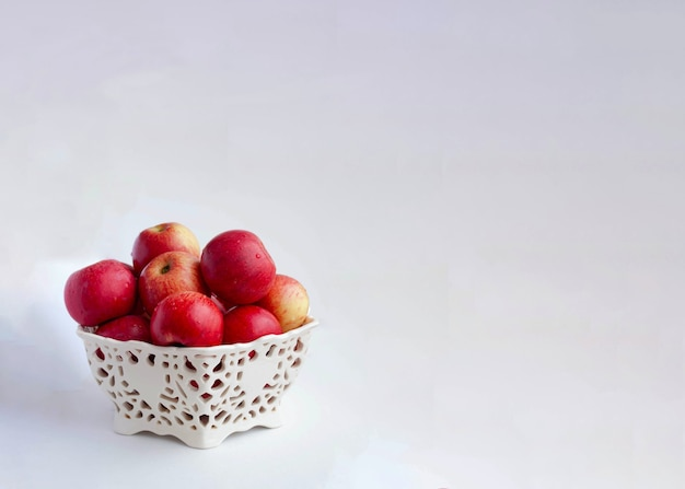 Copispace red apples in a beautiful plate on a white background.