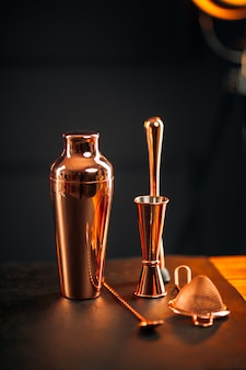 Copper bar tools set with shaker on wooden table