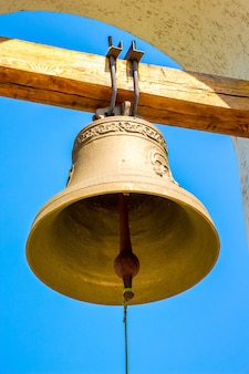 Copper bell on the bell tower of the orthodox church on the background of the blue sky on a sunny day