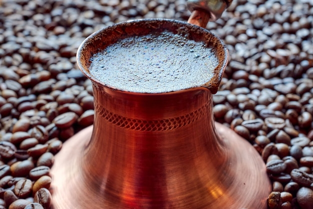 Copper cezva with freshly brewed coffee close-up