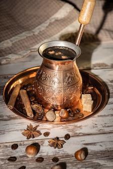 Медная турка с кофе, кофейный натюрморт в теплых тонах