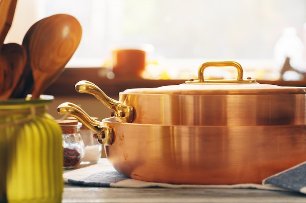 Copper cookware with wooden kitchen utensils close up