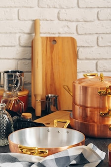 Copper cookware with wooden kitchen utensils