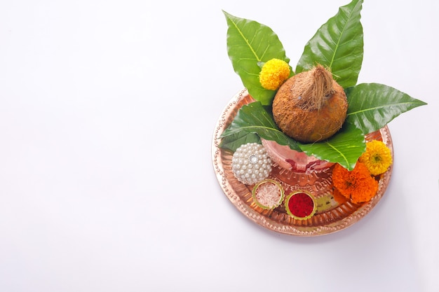 Copper kalash with coconut, leaf and floral decoration on white