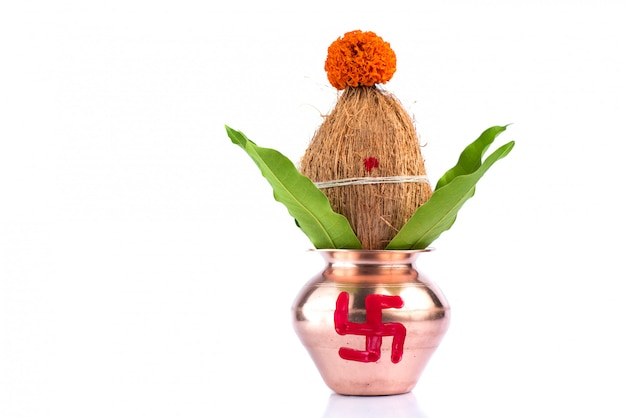 Copper kalash with coconut and mango leaf with floral decoration on a white background. essential in hindu puja.