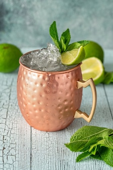 Copper mug of moscow mule cocktail garnished with mint and lime