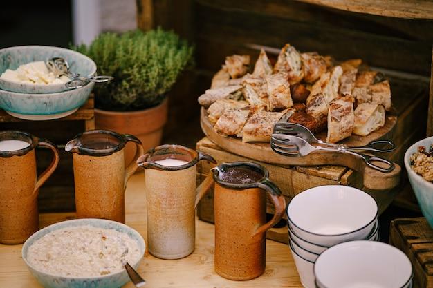 Медные кружки с молоком и горячим шоколадом на столе у тарелки с молочной кашей и фреш
