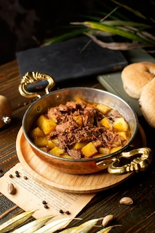 Copper pan with potato and lam stew cooked in oil
