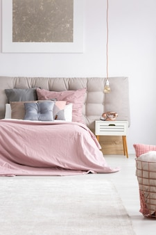 Copper phone on white nightstand next to king-size bed with pink overlay in elegant bedroom