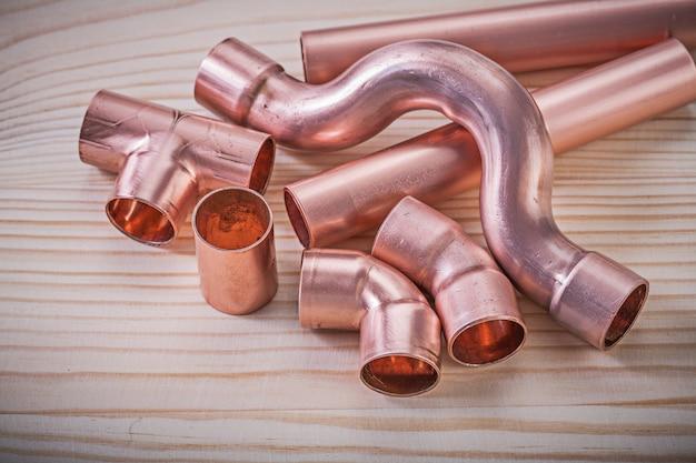 Copper pipe fixtures on wooden board plumbing brassware concept