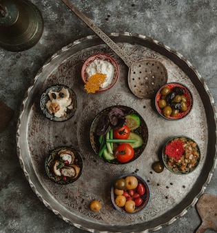 A copper plate of selection of marinated foods.
