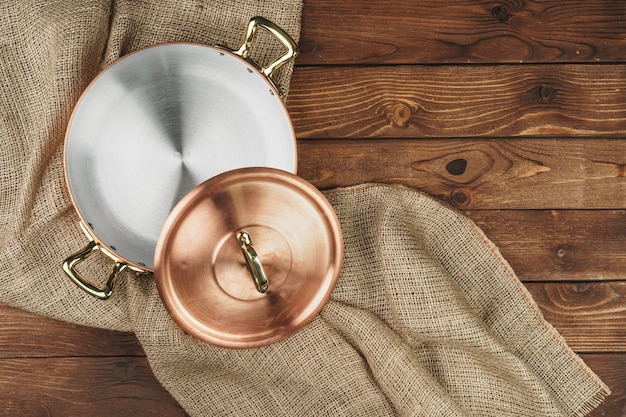 Copper pot on the dark wooden table, top view