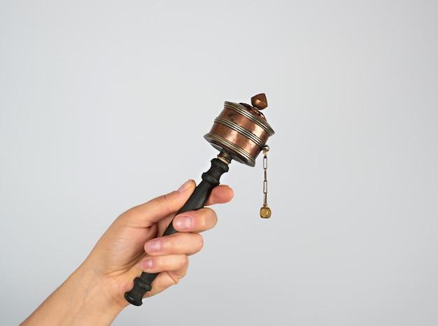 Медный молитвенный барабан на палочке в женской руке