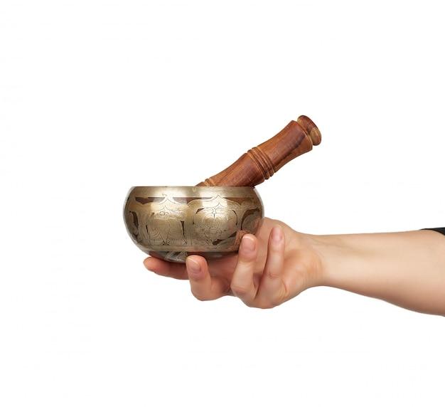 Медная поющая чаша и деревянная палочка в женской руке