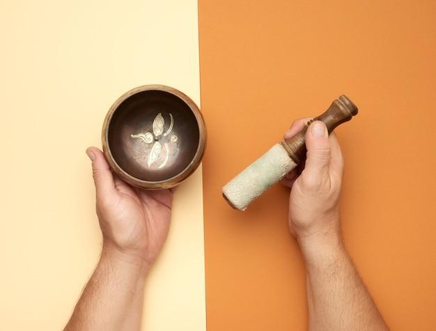 Медная поющая чаша и деревянная палочка в мужской руке, вид сверху