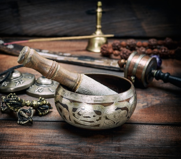 Copper singing bowl and a wooden stick on brown table