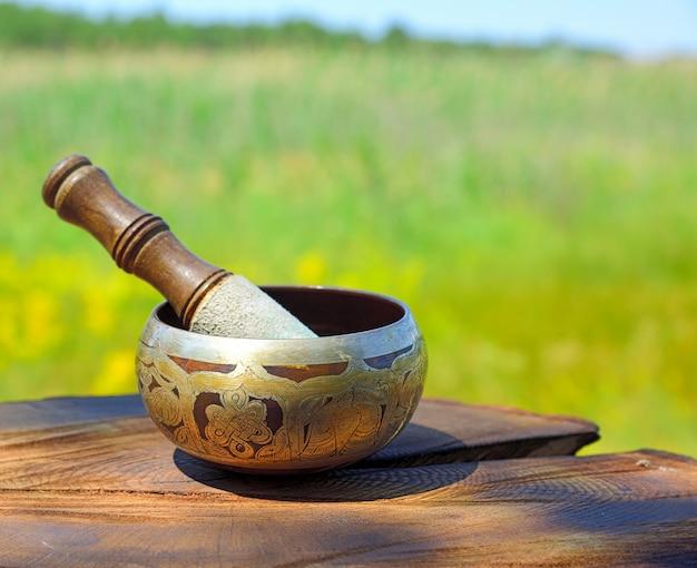 Медная тибетская поющая чаша на коричневом деревянном фоне, размытый фон
