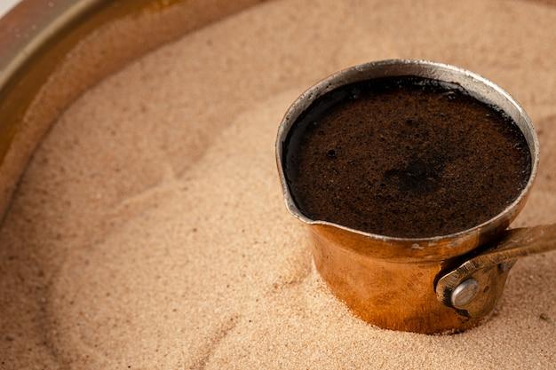 Медная турка с кофейной заваркой в песке