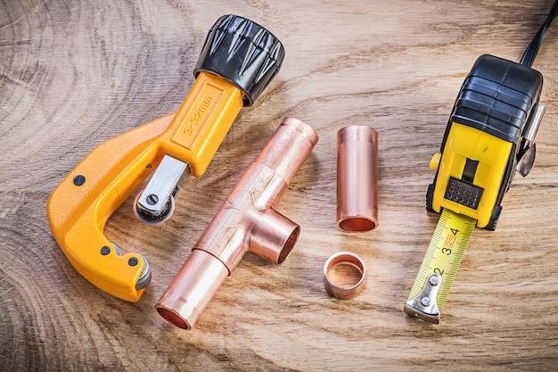 Copper water pipe cutter connectors tape measure on wood board plumbing brassware concept