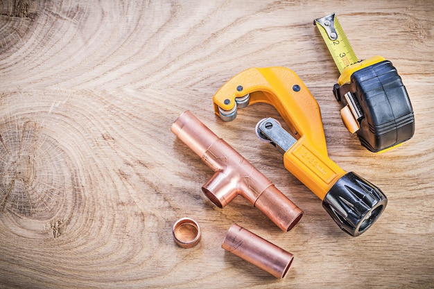 Copper water pipe cutter fittings tape measure on wood board top view plumbing brassware concept