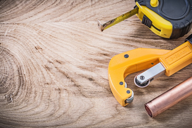 Copper water pipe cutter measuring tape on wooden board plumbing concept