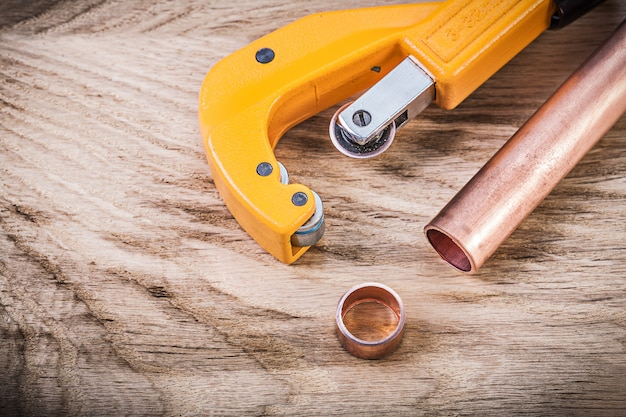 Copper water pipe cutter on wooden board plumbing brassware concept