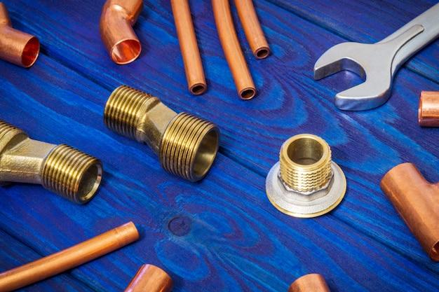 銅の水パイプ継手と配管の概念をはんだ付けするためのツールまたはヴィンテージの青い木の板の水の供給を修復
