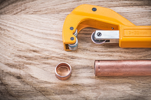 Copper water pipe scissors on wooden board plumbing brassware concept