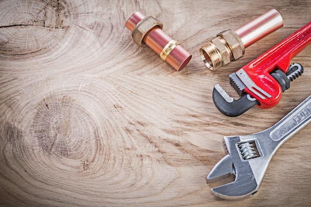 Медный водопроводный шланг с резьбой ниппели гаечный ключ разводной ключ на деревянной доске сантехника концепции