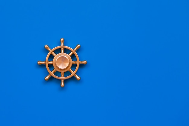 Copper yacht steering wheel on blue background with symbol of leadership