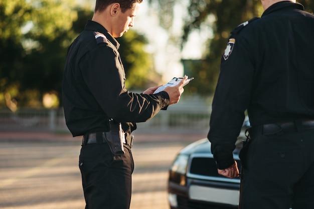 制服を着た警官が道路で車を止める
