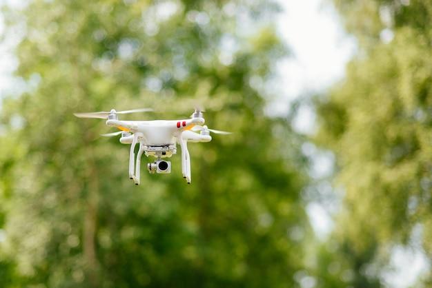 Copter с цифровой камерой, летящей высоко в воздухе, фотографируя