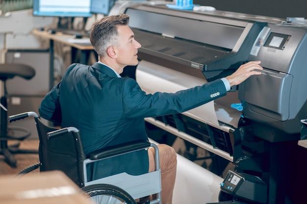 コピー機。オフィスのコピー機に触れる車椅子のビジネスジャケットの深刻な関心のある男性のプロファイル