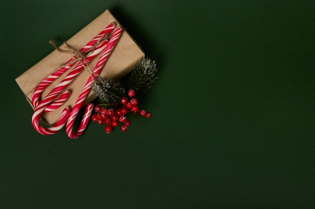 Copy space for advertisement on a dark green background with christmas present in craft wrapping gift paper ornated with holly and sweet sugary striped white and red lollipops candy canes