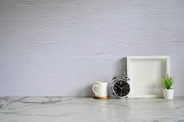 Copy space alarm clock. coffee, photo frame and plant decoration on white marble table and brick wall.