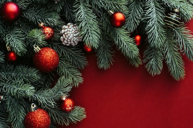 빨간색 배경에 크리스마스 장식과 공 크리스마스 트리 분기 사이의 공간을 복사