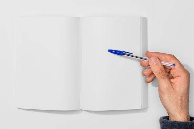 Copy space book and person holding a pen