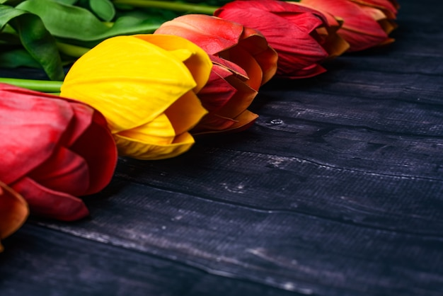 Copy space bouquet of orange and yellow tulips over a rustic wood table top