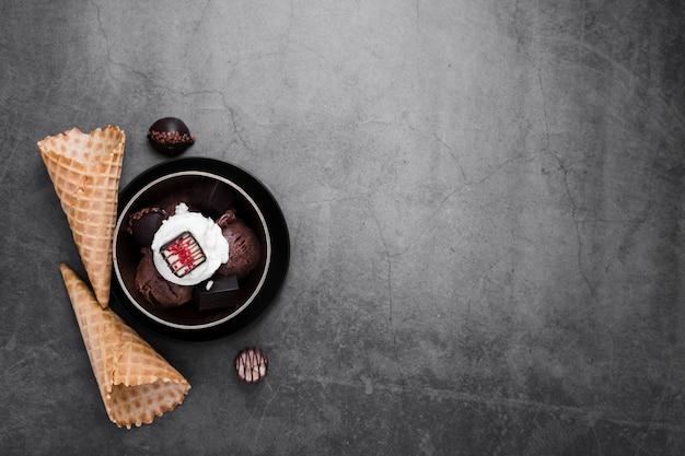 Copy-space bowl with ice cream scoops beside ice cream cones