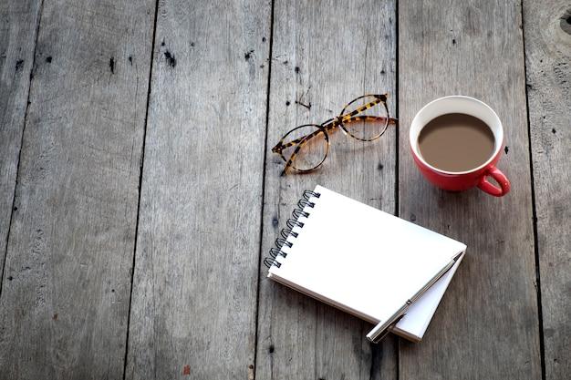 Copia spazio di taccuino vuoto e tazza di caffè rosso su sfondo di legno