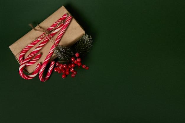 濃い緑色の背景に広告用のスペースをコピーし、ホリーと甘い甘い縞模様の白と赤のロリポップキャンディケインで飾られたクラフトラッピングギフトペーパーにクリスマスプレゼントを添えて