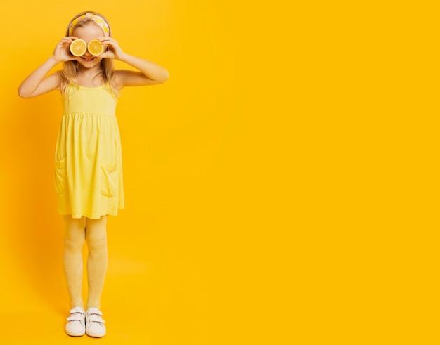 レモンスライスで目を覆っているコピースペースの女の子